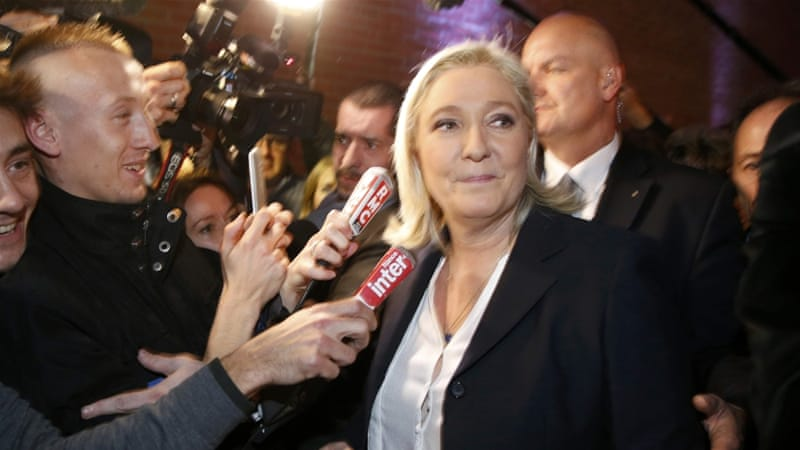 French National Front political party leader and candidate Marine Le Pen surrounded by media [REUTERS]