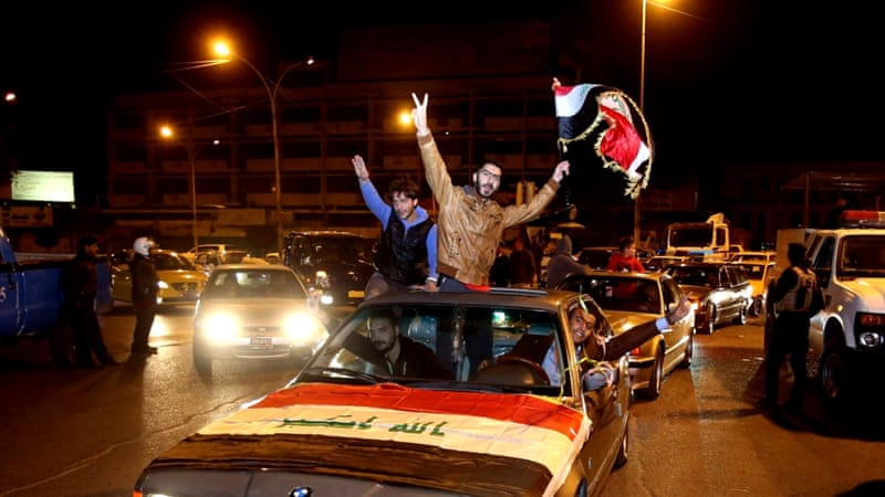 Iraqis celebrate after the lifting of the night curfew at Tahrir Square in Baghdad [AP]