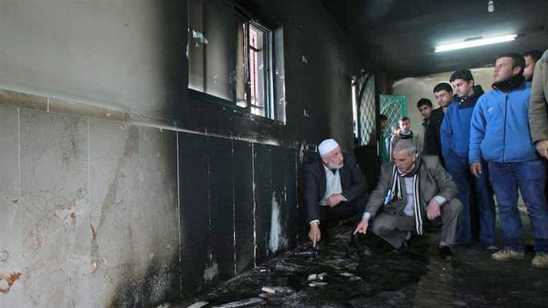 Palestinians inspect the damage at a mosque that was torched overnight in the West Bank village of al-Jaba [Getty Images]