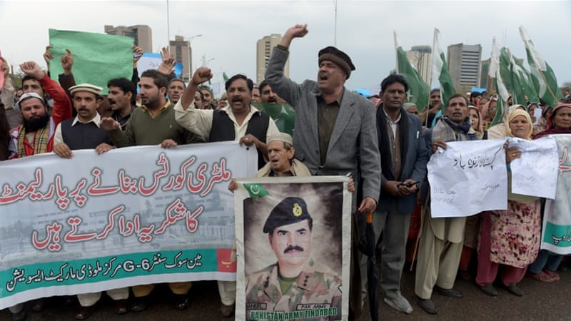 A Pakistani civil society worker carries a photograph of Pakistan's army chief during a peace rally in Islamabad [AFP]