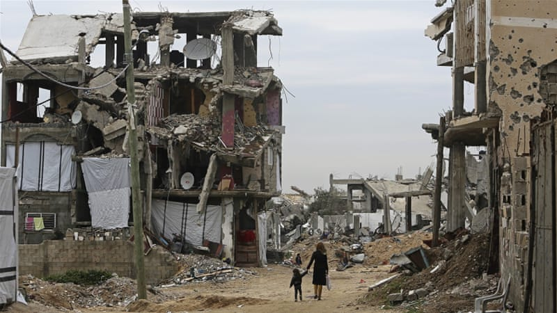 Palestinian children walk between the rubble of buildings which were destroyed during the summer war in Gaza City [AP]