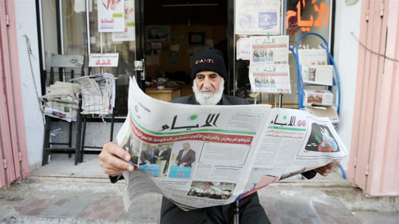 A Palestinian man reads a local newspaper, which features the Israeli election on its front page, in the southern Gaza Strip [REUTERS]