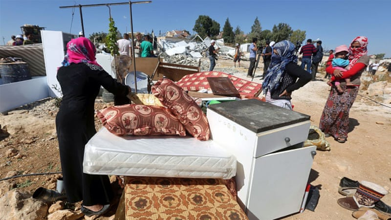 Palestinian Bedouins collect their possessions after their dwelling was demolished by Israeli security forces [EPA]
