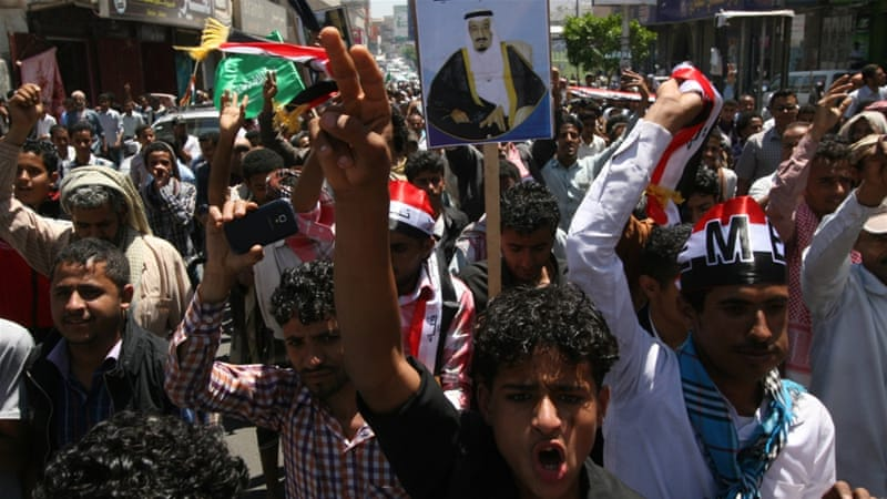 Yemenis hold a poster of King Salman as they chant slogans at a rally in support of Saudi-led airstrikes against Houthis [AP]