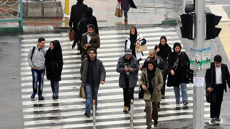 Iranians walk on a street in the capital Tehran [Getty]