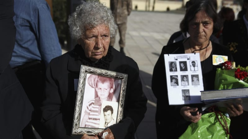 Greek Cypriot women hold photos of relatives missing since 1974, at Tymvos Macedonitissas military cemetery in Nicosia [Reuters]