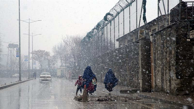 Burqa-clad Afghan women and a child walk in a snow storm in Kabul, Afghanistan [AP]