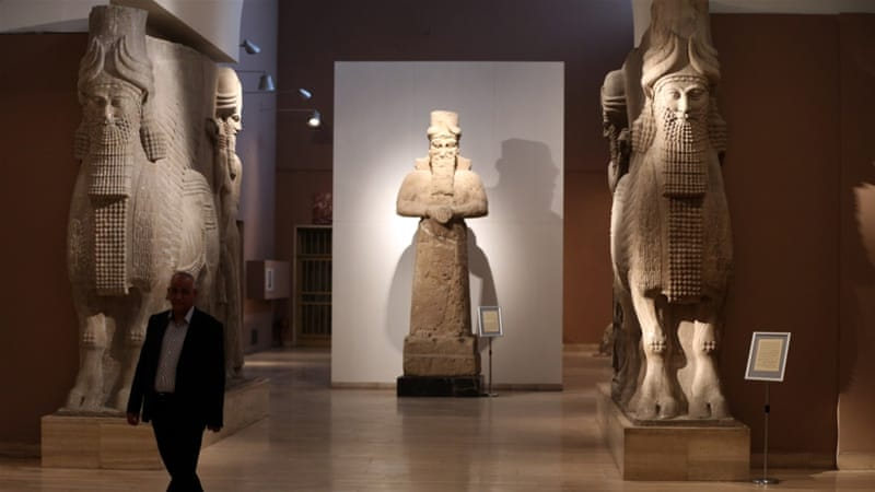 A man at Iraq's National Museum in Baghdad walks past two ancient Assyrian human-headed winged bull statues [AP]