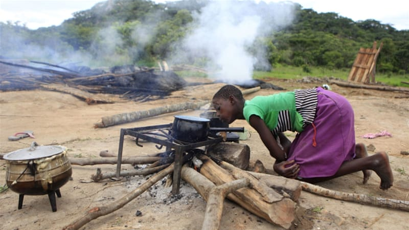 A Zimbabwean girl prepares food besides burnt and demolished makeshift shelters at Manzou Farm in Mazowe [REUTERS]
