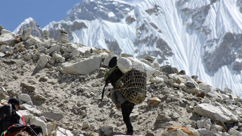 A porter ascends towards Everest Base Camp with Mount Everest seen in the background at Gorakshep, Nepal [AP]