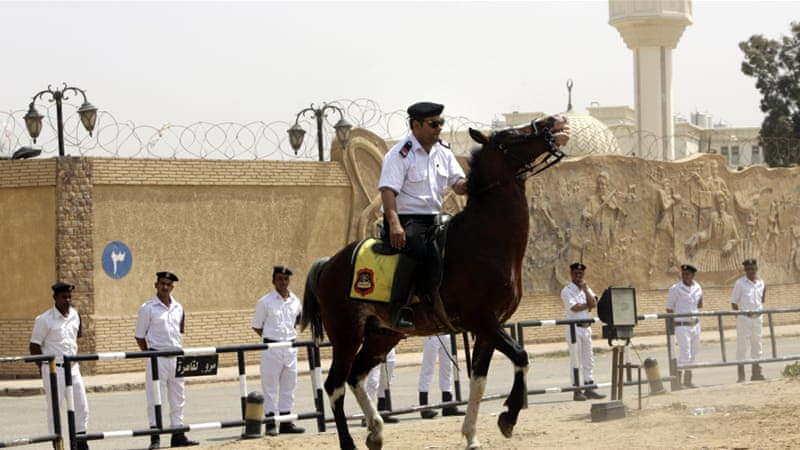 Egyptian policemen secure Egypt's national police academy, where a court sentenced Morsi to 20 years in prison [AP]