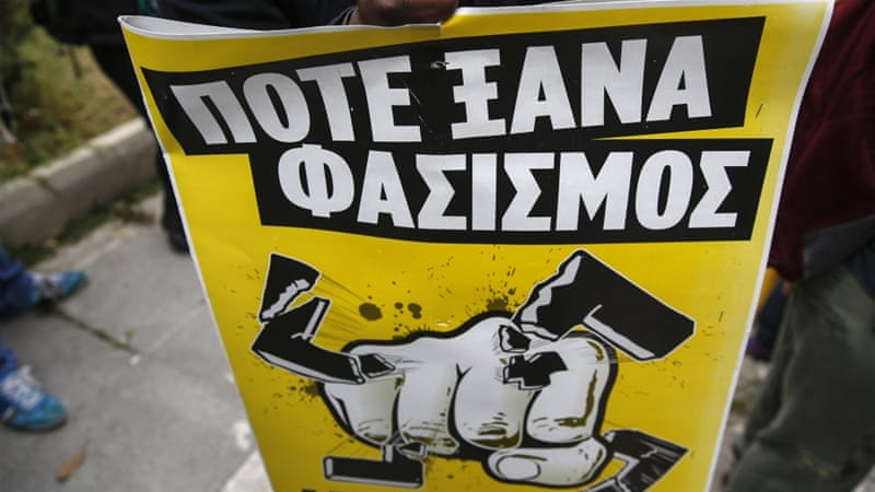 An anti-fascist protester holds a banner that reads: 'Never Again Fascism', during a rally in a suburb near Athens [AP]