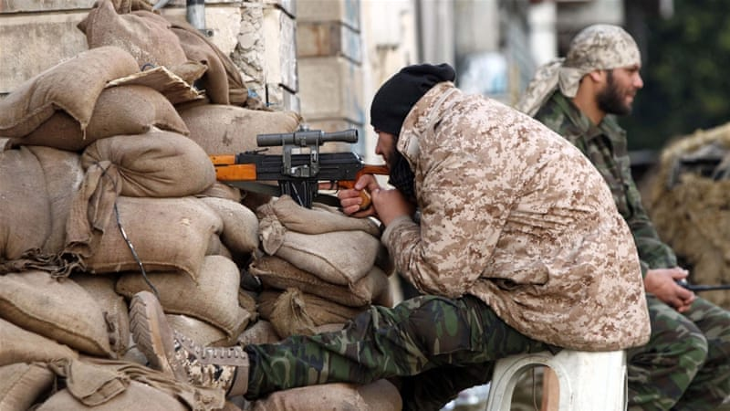 A Libyan soldier monitors a street from his sniper nest in Benghazi [AFP]