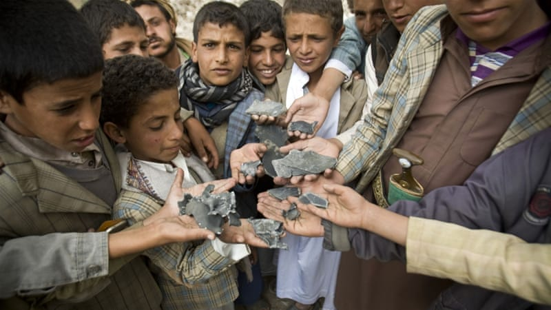 Yemeni boys display shrapnel they collected from the rubble of houses destroyed by air strikes in a village near Sanaa [AP]