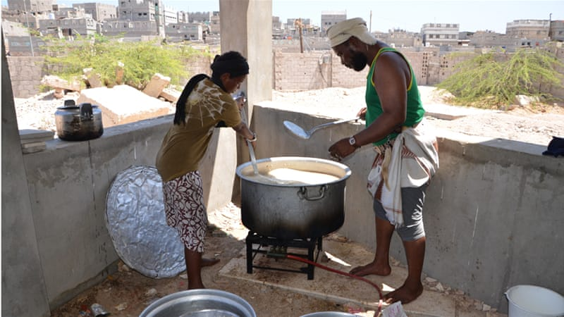 Local volunteers prepare lunch for displaced residents in the port city of Mukalla [Saeed Al Batati/Al Jazeera]