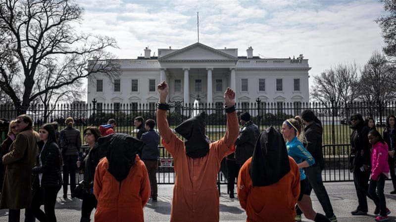 Protesters dressed as Guantanamo Bay prisoners take part in an anti-war demonstration [Reuters]