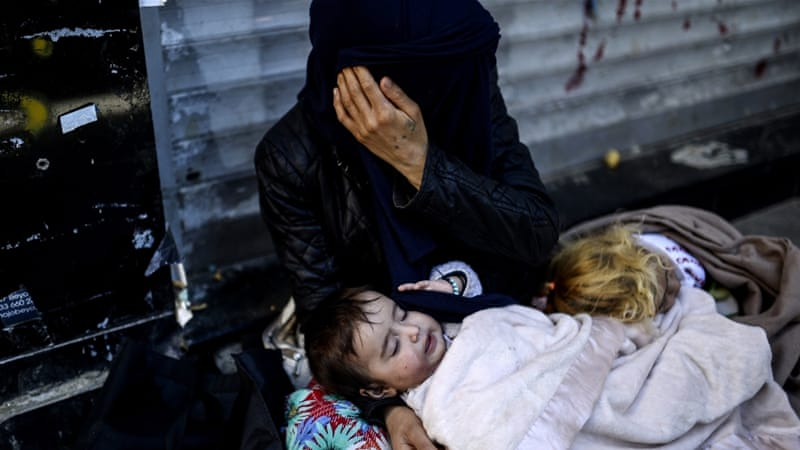 A Syrian refugee woman covers her face as she begs with her children on the street in the Beyoglu district of Istanbul [AFP]