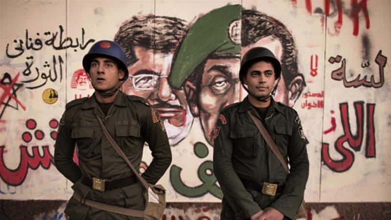 Egyptian soldiers stand in front of graffiti on the walls of the Presidential Palace in Cairo [AFP]