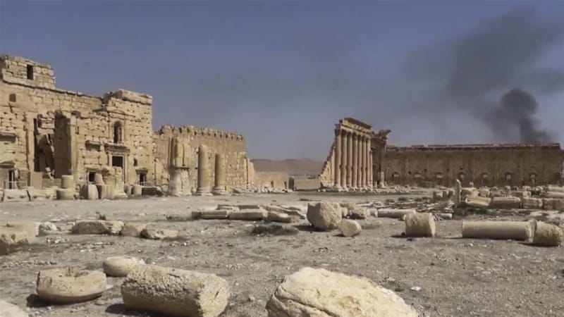 Smoke rises behind archaeological ruins in Palmyra, Syria [AP]