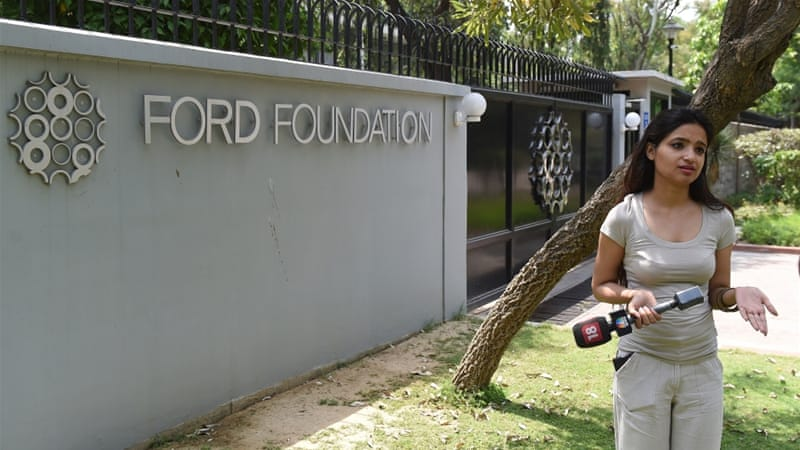 An Indian television journalist reports outside the office of the Ford Foundation in New Delhi [AFP]