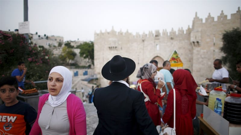 A Muslim woman and an ultra-orthodox Jewish man walk near the Damascus Gate in Jerusalem's Old City [REUTERS]