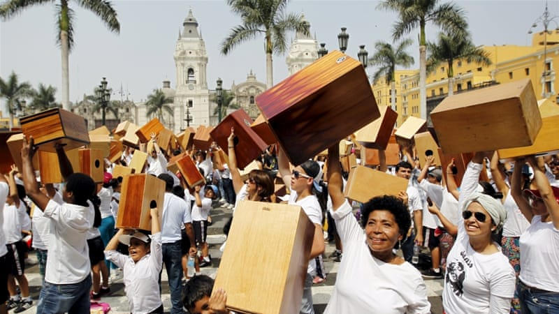 Peruvians hold up their cajones, a traditional musical instrument, in celebration [Reuters]