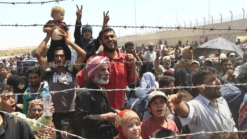 Syrian refugees mass at the Turkish border while fleeing intense fighting in northern Syria [AP]