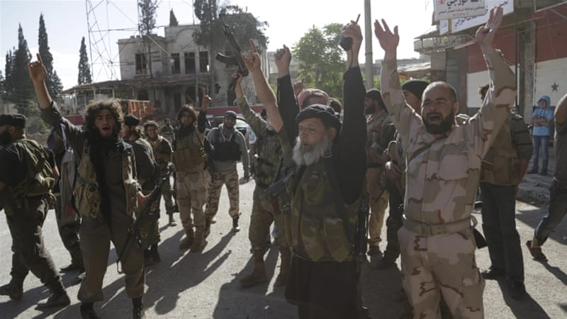 Nusra Front members cheer in the city of Ariha, after a coalition of insurgent groups seized the area in Idlib [REUTERS]