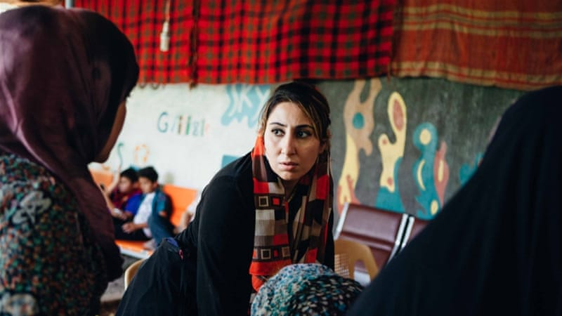 Sara listens to a Syrian refugee in the courtyard of the women's centre [Andrea DiCenzo/Al Jazeera]