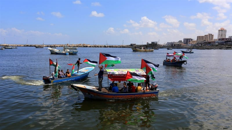 Palestinians carry Palestinian flags on their boats as they gather at the Gaza coast in support of the third Gaza Freedom Flotilla [Getty]