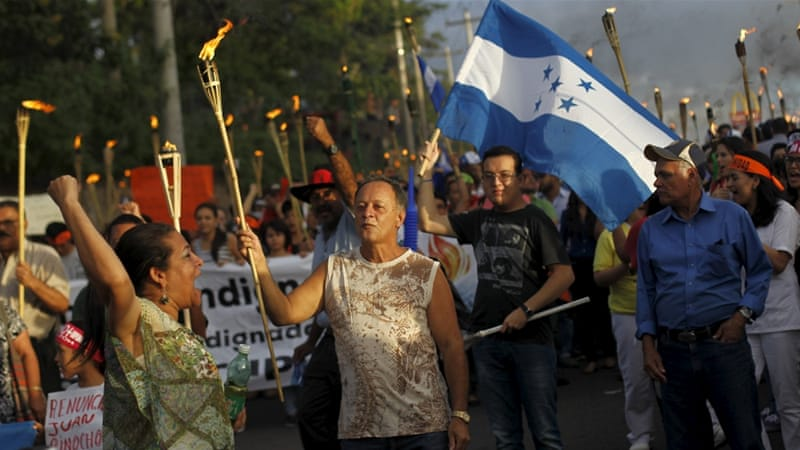 People take part in a march to demand the resignation of Honduras' President Juan Hernandez in Tegucigalpa [Reuters]