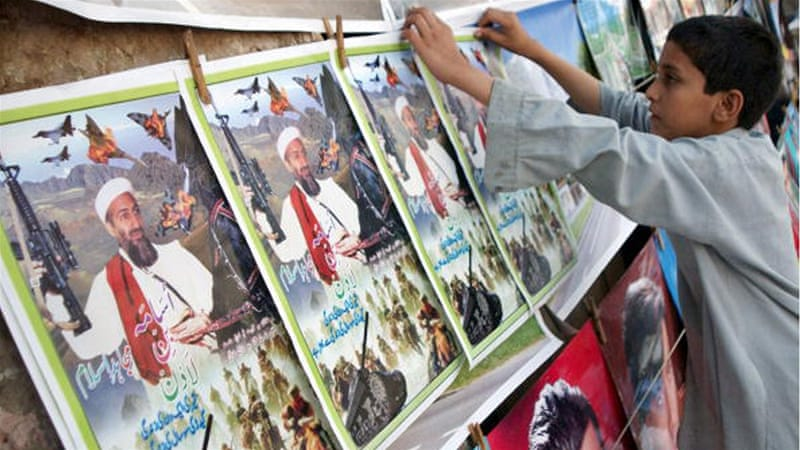 A Pakistani vendor hangs posters of Osama bin Laden at his roadside bookstall in Peshawar [AFP]