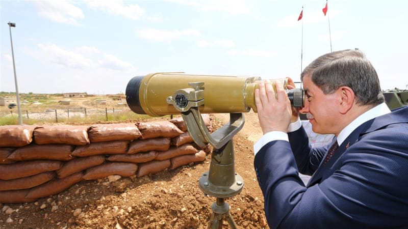 Turkish prime minister looks through binoculars at Syria from a Turkish military base at the border with Syria [Reuters]