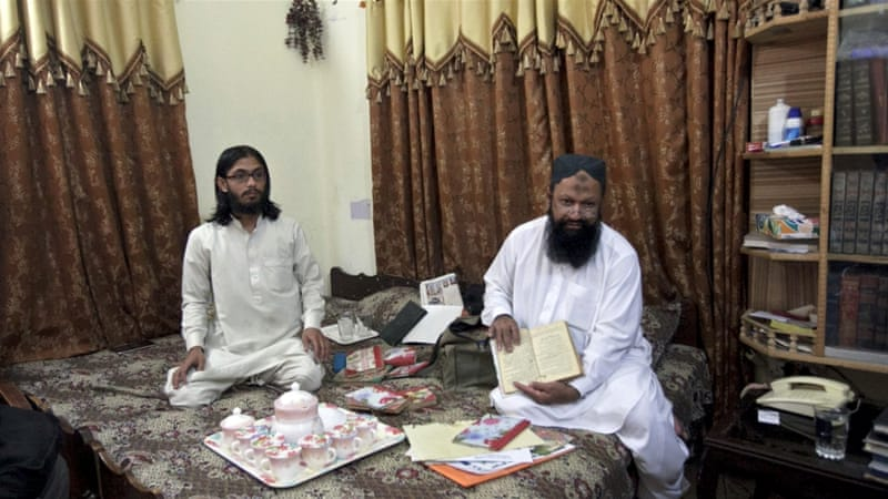 Malik Ishaq (R) sits on a bed with his son Malik Usman during an interview with Reuters at his home in Rahim Yar Khan [Reuters]