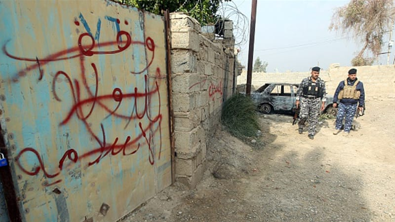Iraqi policemen cross out out graffiti reading 'property of ISIL' [Getty]