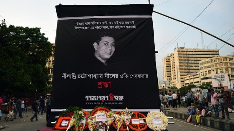Floral wreaths are placed below a banner during a protest against the killing of blogger Niloy Chatterjee [AFP]