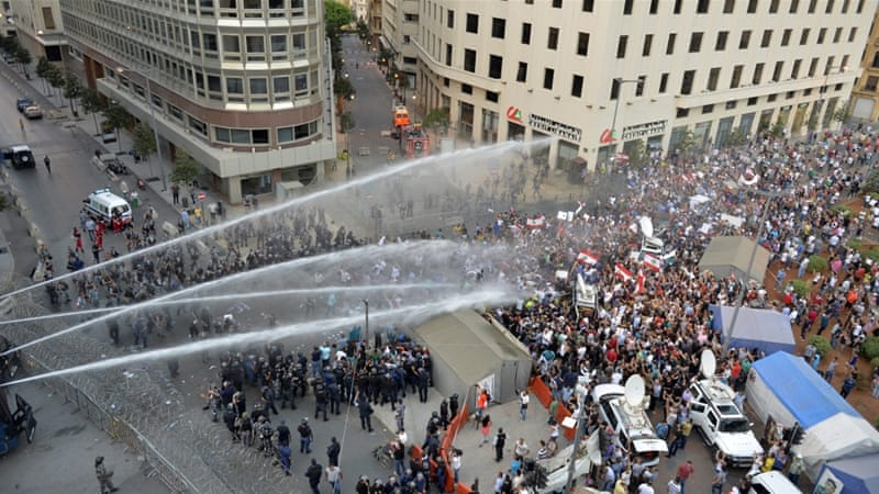 Riot police on Saturday used batons to beat back protesters in downtown Beirut [EPA]
