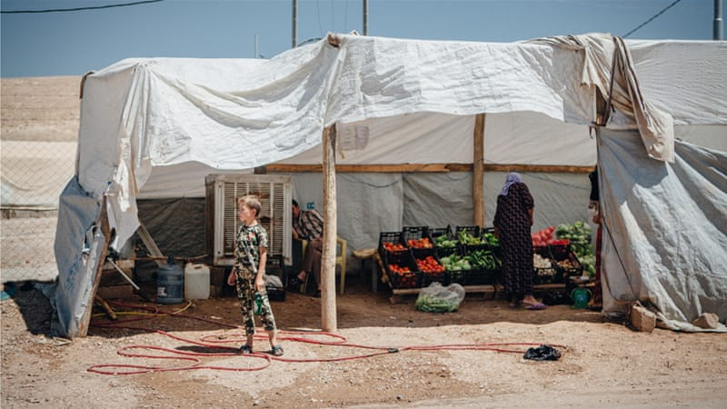 A woman buys fruits and vegetables at a roadside shop in the Esyan refugee camp for internally displaced Yazidis [Andrea DiCenzo/Al Jazeera]