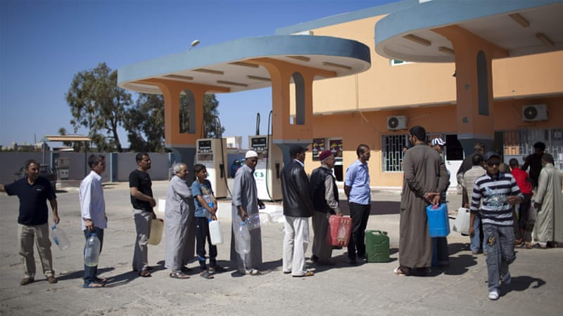 Residents of Benghazi must wait in long queues to buy petrol, while daily blackouts last for several hours [AP]
