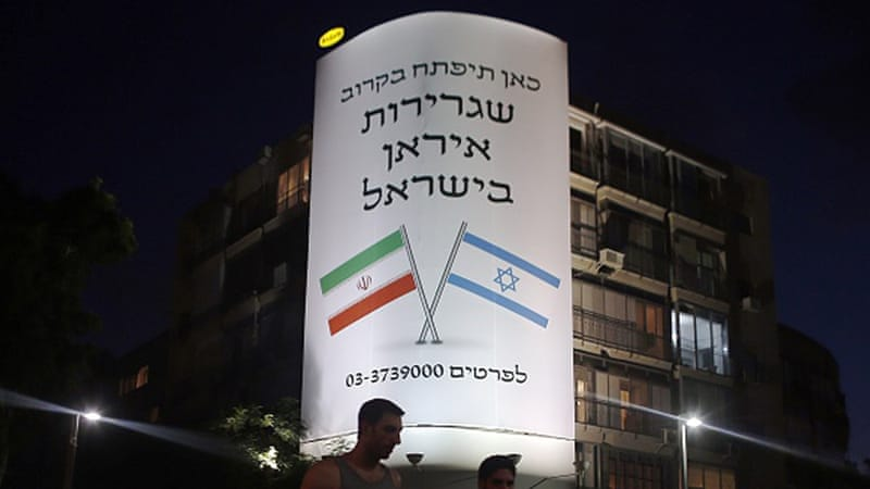 A large billboard depicting the flags of Israel and Iran reads 'The Iranian embassy in Israel will open soon,' in central Tel Aviv [AFP]