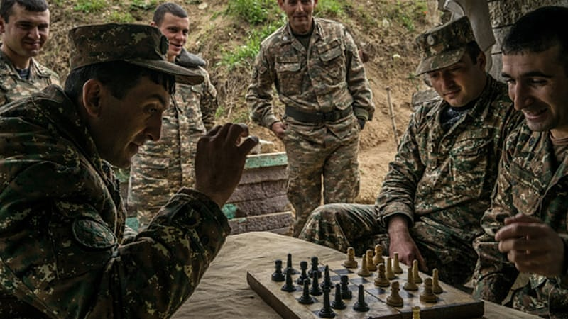 Nagorno-Karabakh armed forces play checkers using a chess set at their post along the line of contact with Azerbaijani forces [Getty]