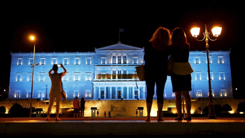 People stand in front of the parliament building illuminated with blue lights in Athens, Greece [REUTERS]
