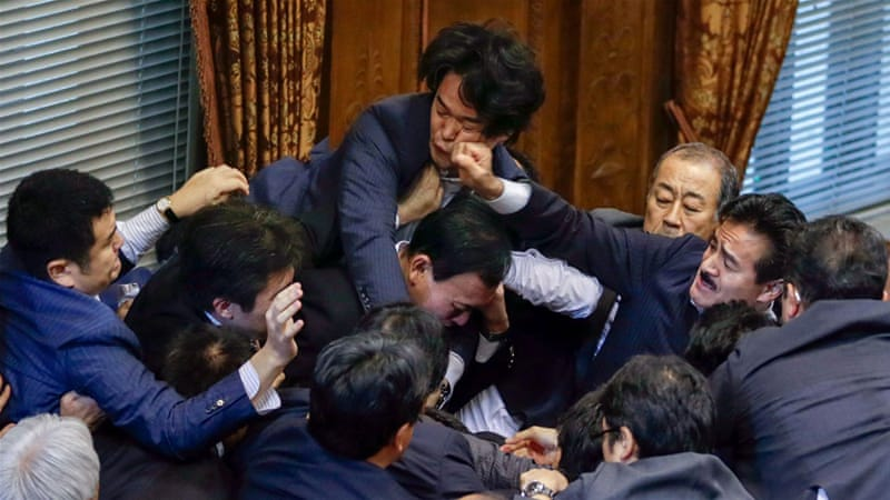 There were scuffles in parliament as protesters and politicians tried to physically stop the motion [EPA]