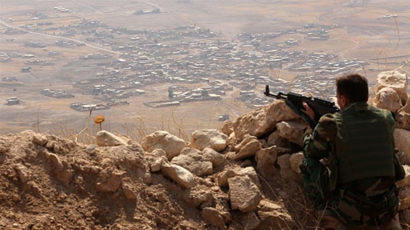 An Iraqi Kurdish Peshmerga fighter monitors his surrounding from the top of Mount Zardak, about 25km east of Mosul [AFP]