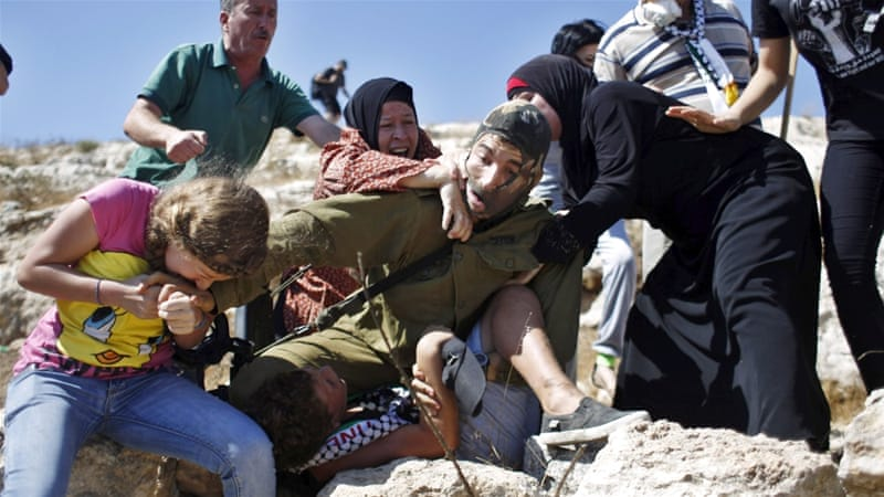 Palestinians scuffle with an Israeli soldier as they try to prevent him from detaining a boy in the village of Nabi Saleh [REUTERS]