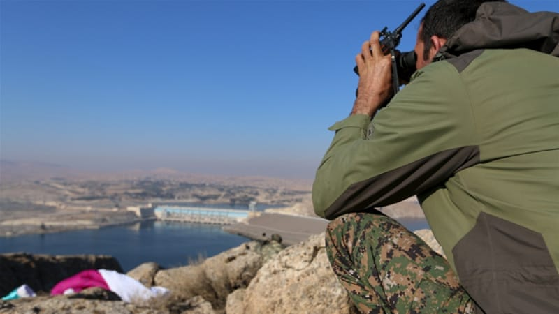 A fighter from the Democratic Forces of Syria takes an overwatch position overlooking the Tishrin dam [Rodi Said/Reuters]