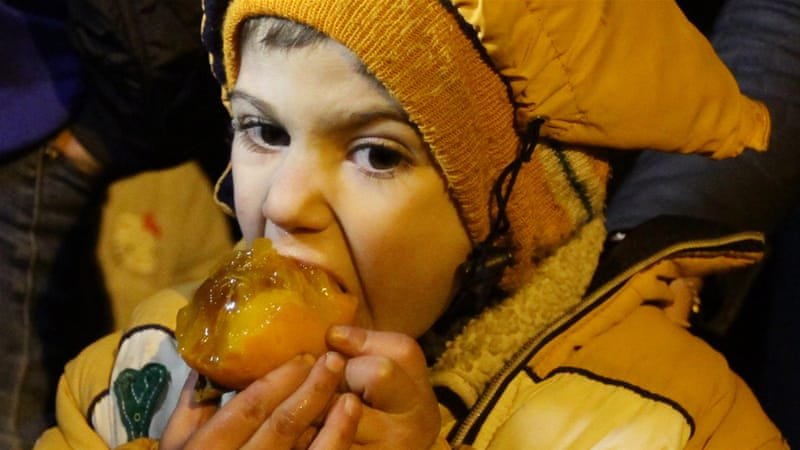A Syrian child eats fruit on the outskirts of the besieged rebel-held Syrian town of Madaya after aid arrived last month [AP]