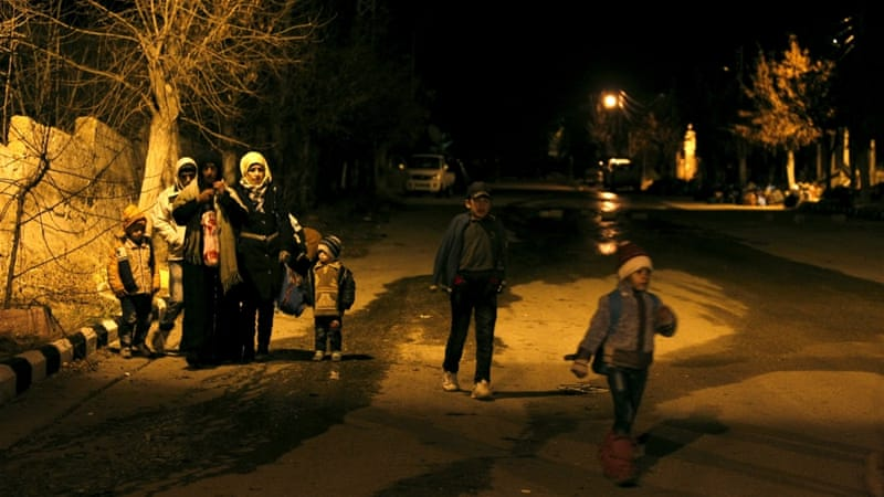 Residents of besieged Madaya wait to leave the town after receiving government permission  [Omar Sanadiki/Reuters]