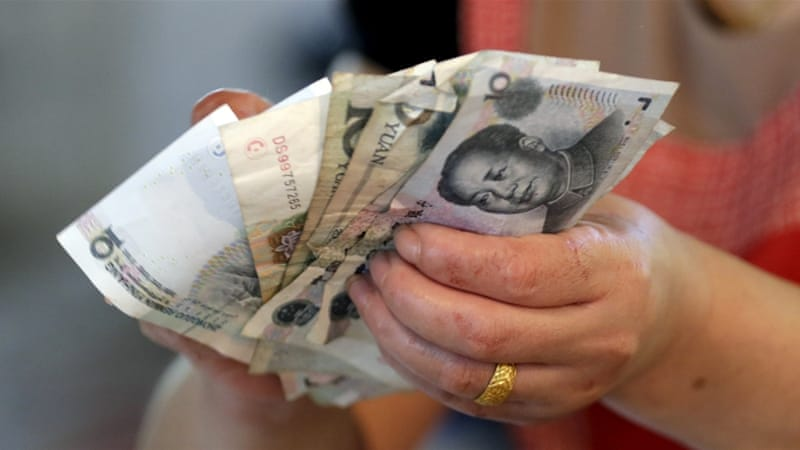 A vendor holds Chinese Yuan notes at a market in Beijing [Reuters]