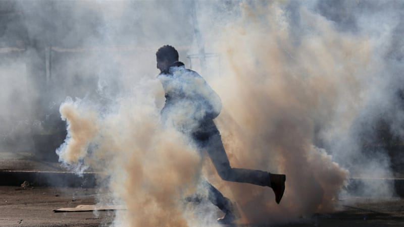 A Palestinian protester runs for cover from tear gas fired by Israeli troops during clashes in the West Bank city of Bethlehem [REUTERS]
